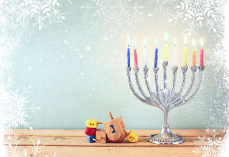 hanuka: image of jewish holiday Hanukkah with menorah traditional Candelabra and wooden dreidels spinning top. retro filtered image with glitter and snowflakes overlay Stock Photo
