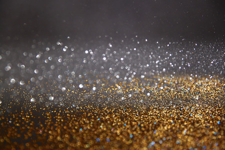 glowing: glitter vintage lights background. gold, blue and black. defocused