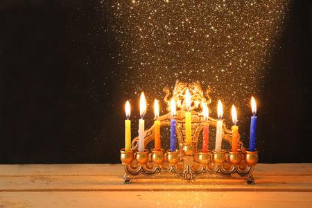 hanukka: Image of jewish holiday Hanukkah background with menorah traditional candelabra Burning candles over black background and glitter lights Stock Photo
