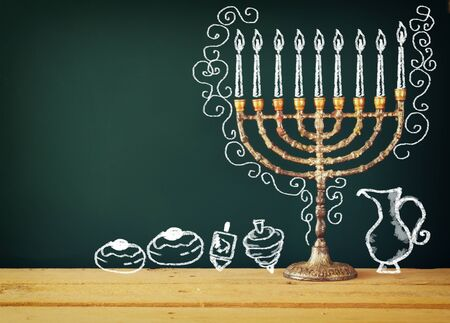 hanukka: image of jewish holiday Hanukkah with drawing menorah candles traditional Candelabra, donuts and dreidels spinning top over chalkboard background Stock Photo