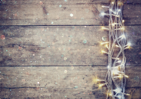 Christmas warm gold garland lights on wooden rustic background. filtered image with glitter overlay Standard-Bild