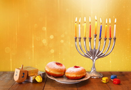 jewish background: low key image of jewish holiday Hanukkah with menorah, doughnuts and wooden dreidels spinning top. retro filtered image Stock Photo