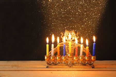 chanukiah: Image of jewish holiday Hanukkah background with menorah traditional candelabra Burning candles over black background and glitter lights Stock Photo