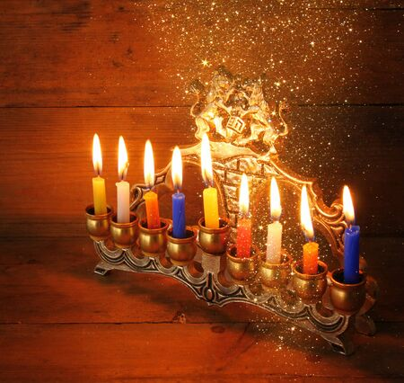 chanukiah: Image of jewish holiday Hanukkah background with menorah traditional candelabra Burning candles over  wooden background and glitter lights Stock Photo
