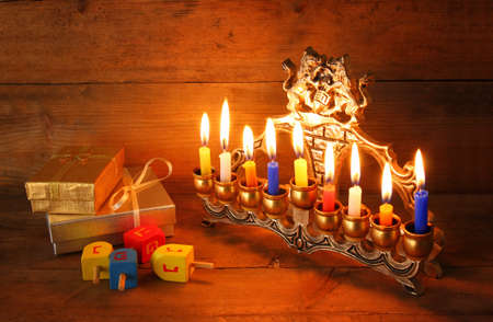 dreidels: low key image of jewish holiday Hanukkah with menorah traditional Candelabra, donuts and wooden dreidels spinning top Stock Photo