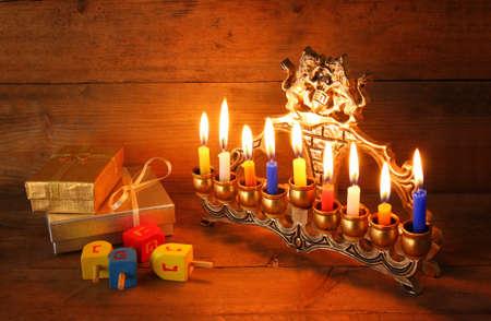 hanuka: low key image of jewish holiday Hanukkah with menorah traditional Candelabra, donuts and wooden dreidels spinning top Stock Photo