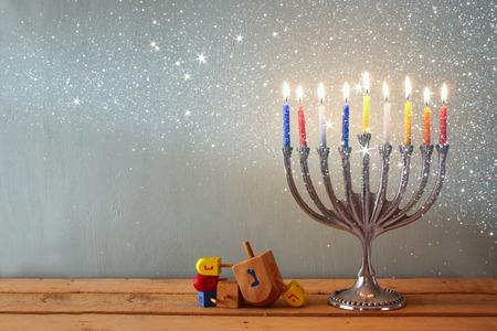 hanoukia: image de f�te juive de Hanoukka avec menorah Candelabra traditionnelle et toupies en bois toupie. R�tro image filtr�e avec des paillettes superposition