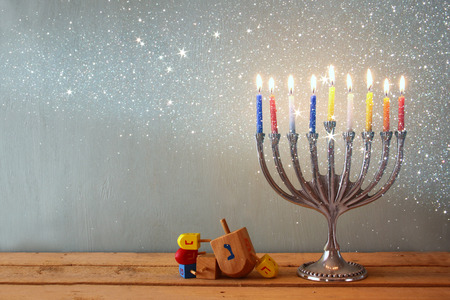 hanukka: image of jewish holiday Hanukkah with menorah traditional Candelabra and wooden dreidels spinning top. retro filtered image with glitter overlay