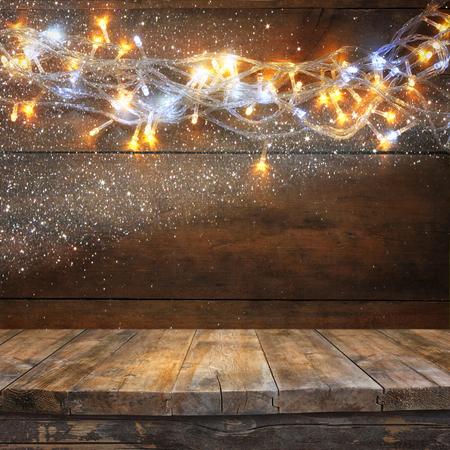houten bord tafel voor Kerstmis warme goud guirlande lichten op houten rustieke achtergrond. gefilterde afbeelding. selectieve aandacht. glitter overlay Stockfoto