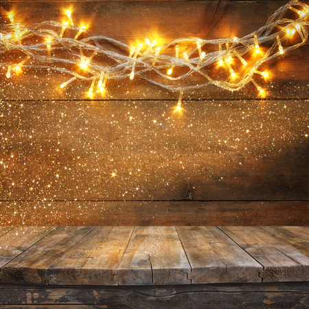 christmas wallpaper: wood board table in front of Christmas warm gold garland lights on wooden rustic background. filtered image. selective focus. glitter overlay