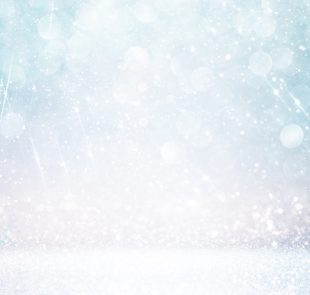 bokeh lights background with multi layers and colors of white silver and blue with snowflakes overlay Stock Photo