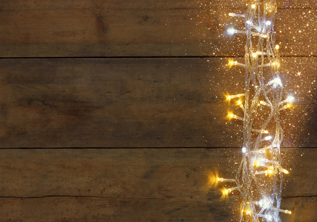 christmas gold: Christmas warm gold garland lights on wooden rustic background. filtered image with glitter overlay Stock Photo