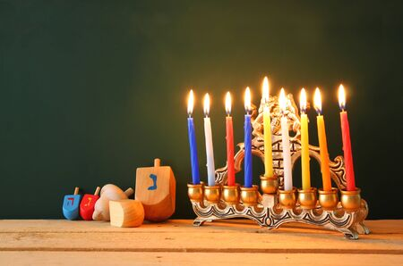 hanukah: low key image of jewish holiday Hanukkah with menorah traditional Candelabra and wooden dreidels spinning top over chalkboard background, room for text Stock Photo