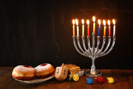 menorah: image of jewish holiday Hanukkah with menorah traditional Candelabra, donuts and wooden dreidels spinning top. retro filtered image