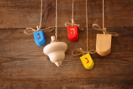 hanukiah: image of jewish holiday Hanukkah with wooden colorful dreidels spinning top hanging on a rope over wooden background Stock Photo