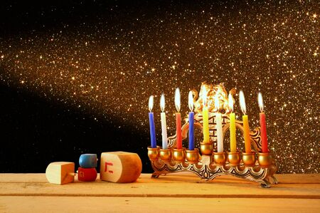 chanukkah: low key image of jewish holiday Hanukkah with menorah traditional Candelabra and wooden dreidels spinning top. glitter overlay Stock Photo