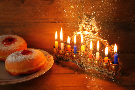 image of jewish holiday Hanukkah with menorah traditional Candelabra, donuts. retro filtered image with glitter overlay Stock Photo