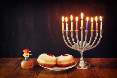 image of jewish holiday Hanukkah with menorah traditional Candelabra, donuts and wooden dreidels spinning top. retro filtered image