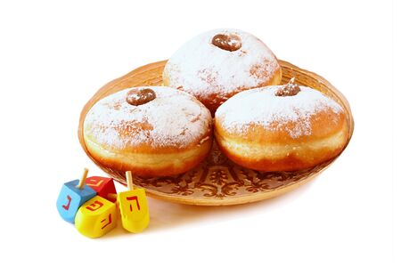 dreidel: image of jewish holiday Hanukkah with donuts and wooden dreidels spinning top. isolated on white