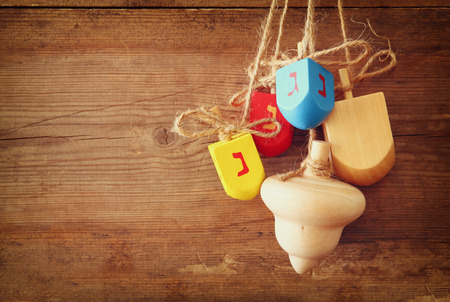 dreidels: image of jewish holiday Hanukkah with wooden colorful dreidels spinning top hanging on a rope over wooden background Stock Photo