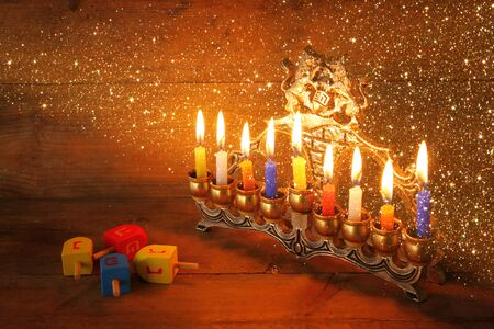 chanukah: low key image of jewish holiday Hanukkah with menorah traditional Candelabra and wooden dreidels spinning top. glitter overlay Stock Photo