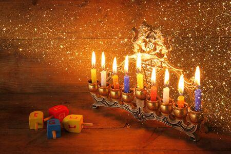 hanuka: low key image of jewish holiday Hanukkah with menorah traditional Candelabra and wooden dreidels spinning top. glitter overlay Stock Photo