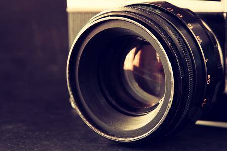 나무 테이블 위에 오래 된 카메라 렌즈의 사진을 닫습니다. 이미지는 복고풍 필터링됩니다. 선택적 포커스