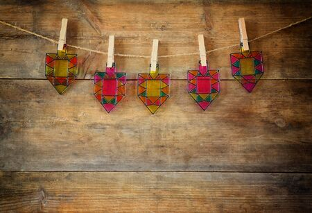 hanukiah: image of jewish holiday Hanukkah with Stained-glass colorful dreidels spinning top hanging on a rope over wooden background