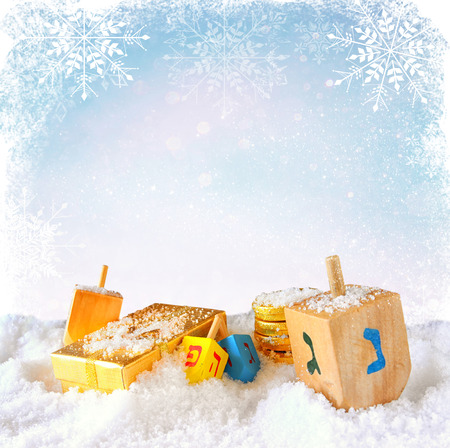dreidels: image of jewish holiday Hanukkah with wooden colorful dreidels spinning top  over december snow with glitter and snowflake background