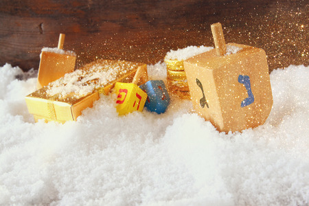 hanukiah: image of jewish holiday Hanukkah with wooden colorful dreidels spinning top and chocolate traditional coins over december snow Stock Photo