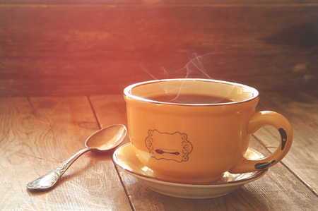 hot drink: cup of coffee on old wooden table.  morning workspace, coffee break .retro filtered image and selective focus