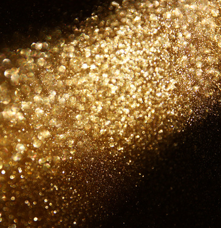 glitter vintage lights background. gold, silver, and black. de-focused.