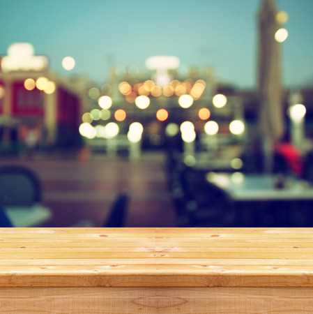 image of wooden table in front of abstract blurred background of resturant lights Stock Photo