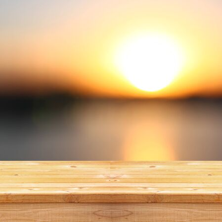 beach sunset: image of textured wood table in front of beach landscape at sunset time Stock Photo