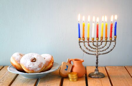 hanoukia: image of jewish holiday Hanukkah with menorah traditional Candelabra, donuts and wooden dreidels spinning top