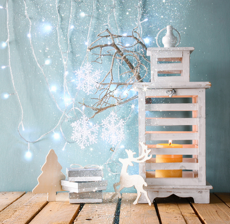 christmas candle: white wooden vintage lantern with burning candle, wooden deer, christmas gifts and tree branches on wooden table. retro filtered image with glitter overlay Stock Photo