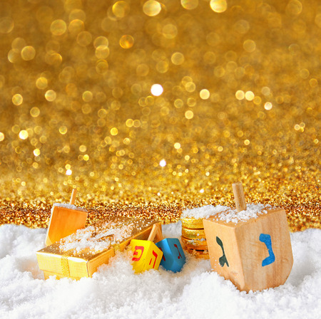 hanukiah: image of jewish holiday Hanukkah with wooden colorful dreidels spinning top and chocolate traditional coins over december snow. glitter background