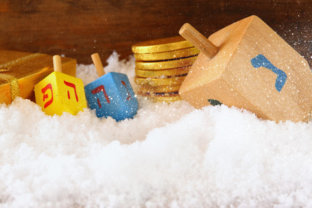 hanoukia: image of jewish holiday Hanukkah with wooden colorful dreidels spinning top and chocolate traditional coins over december snow. glitter overlay