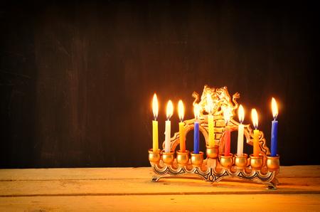menora: Image of jewish holiday Hanukkah background with menorah traditional candelabra Burning candles over black background