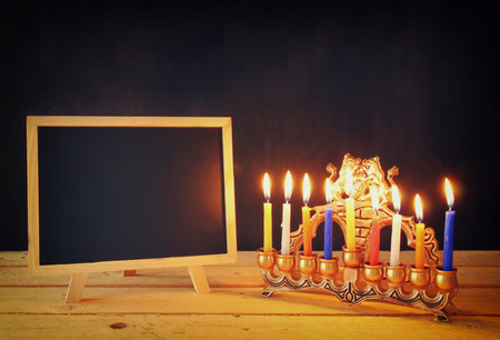 chanukiah: low key image of jewish holiday Hanukkah with menorah traditional Candelabra and wooden chalkboard , room for text