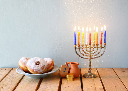 dreidels: image of jewish holiday Hanukkah with menorah traditional Candelabra, donuts and wooden dreidels spinning top. glitter overlay