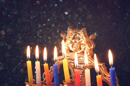 chanukkah: Image of jewish holiday Hanukkah background with menorah traditional candelabra Burning candles over black background with glitter overlay