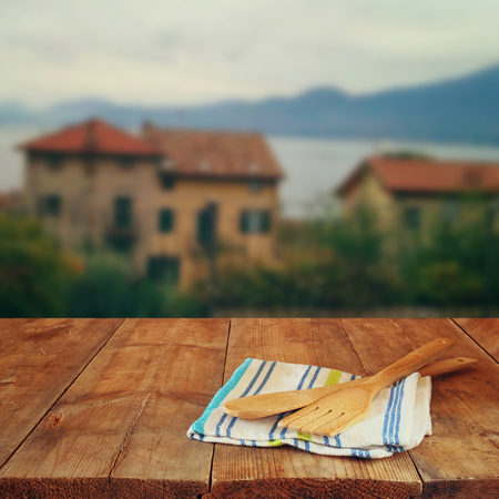 utencils: Kitchen utensils on tablecloth and old wooden table in front of romantic Provence rural landscape. retro filtered image
