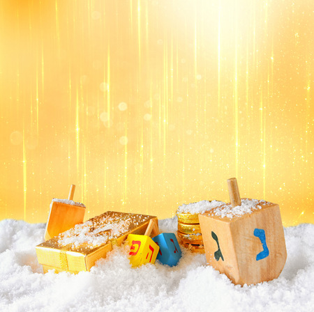 chanukiah: image of jewish holiday Hanukkah with wooden colorful dreidels spinning top and chocolate traditional coins over december snow. glitter background