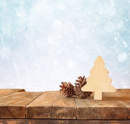 table decoration: abstract image of wooden decorative christmas tree and pine cones on wooden table and christmas holiday bokeh lights