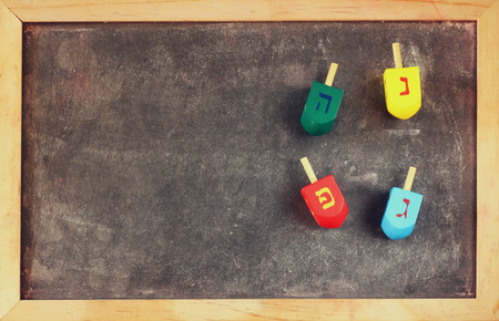 dreidels: image of jewish holiday Hanukkah with wooden colorful dreidels spinning top over chalkboard background Stock Photo