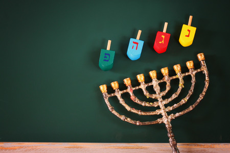 hanoukia: image of jewish holiday Hanukkah with menorah traditional Candelabra and wooden colorful dreidels spinning top over chalkboard background
