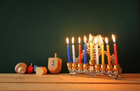 hanukiah: low key image of jewish holiday Hanukkah with menorah traditional Candelabra and wooden dreidels spinning top over chalkboard background, room for text Stock Photo