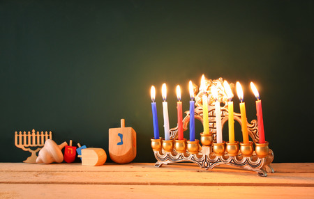 jewish festival: low key image of jewish holiday Hanukkah with menorah traditional Candelabra and wooden dreidels spinning top over chalkboard background, room for text Stock Photo