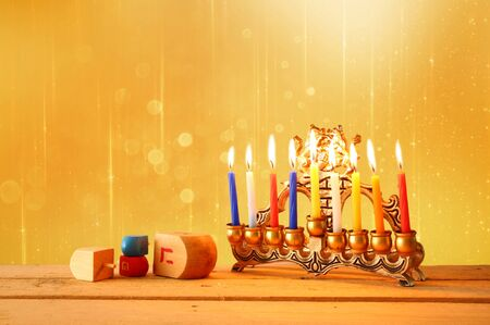dreidels: image of jewish holiday Hanukkah with menorah traditional Candelabra and wooden dreidels spinning top. retro filtered image Stock Photo